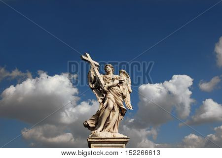 Beautiful angel statue holding the Holy Cross with heavenly sky and copy space from Sant'Angelo Bridge in the historic center of Rome (17th century)