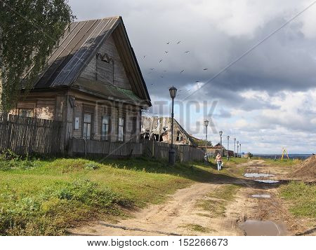 Old wooden house in russian village road puddles