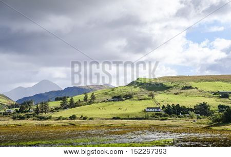 Beautiful colors of rural Isle of Skye landscape on an overcast day. From loch shore at low tide to the green rolling hills of the countryside and the Cuillin mountain range