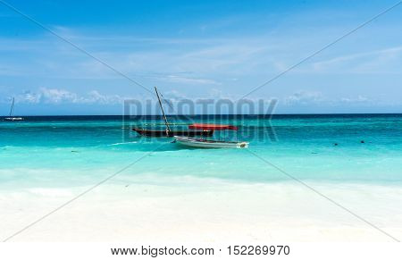 colorful landscape with blue sky and turquoise ocean with sailing boats, view from the beach, Zanzibar