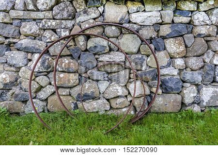 Rusting metal hoops against old lichen covered stone wall with grass and weeds foreground