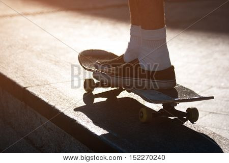 Legs riding a skateboard. Feet wearing slip-on shoes. Feel the rush of adrenaline. Forget the fear.