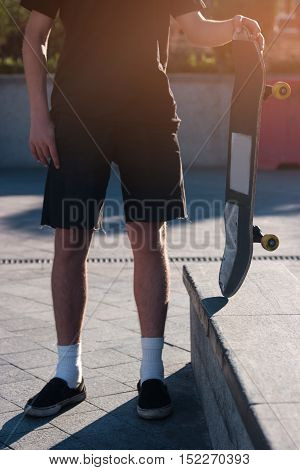 Person holding a skateboard. Skater on outdoor background. Not just a hobby. Sport that inspires youth.