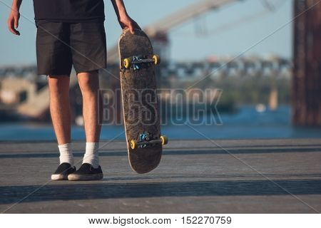Guy with a skateboard. Skateboarder on blurred background. Born to skate. Sport in my blood.