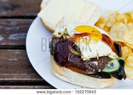 Tasty hamburger and crisps with a BBQ sauce drizzled over a fried egg.on a wooden slatted table.