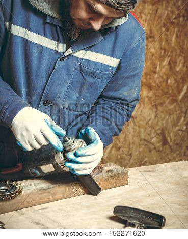 Man carpenter in repairing their working tools in his workshop