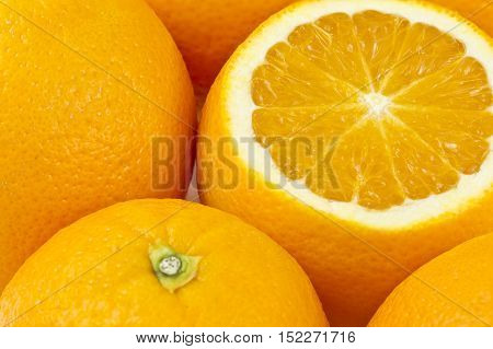 beautiful succulent citrus oranges together in a group with one which has been sliced open