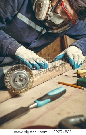Man carpenter polishing wooden bar in his home workshop