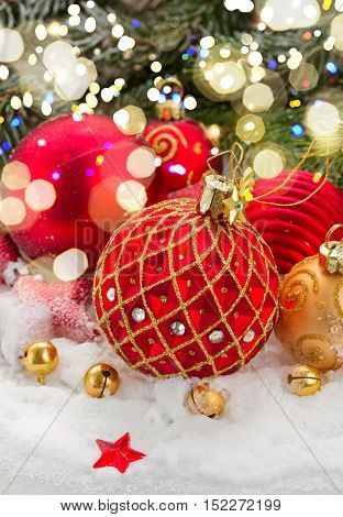 red and gold christmas ball in snow under fir evergreen tree with lights bokeh