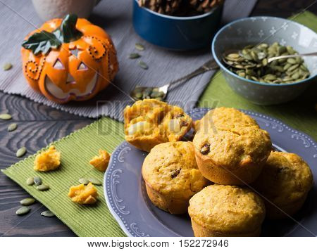 Pumpkin whole grain muffins with raisins and pumpkin seeds on dark background with a halloween decorative squash