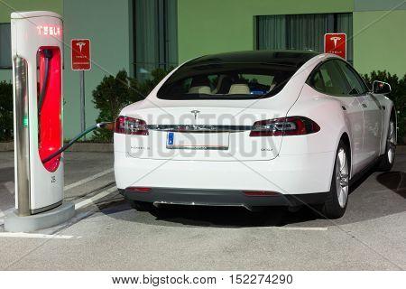 LJUBLJANA SLOVENIA - October 13 2016: Tesla car supercharger machine at Supercharger Station with white Tesla car