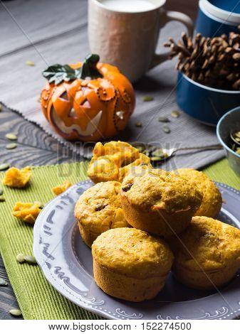Pumpkin whole grain muffins with raisins and pumpkin seeds on dark background with a halloween decorative squash. Vertical image