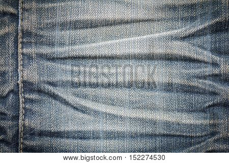 Denim jeans texture or denim jeans background with seam. Old grunge vintage denim jeans. Stitched texture denim jeans background of jeans fashion design. Dark edged.