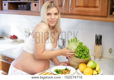 young pregnant woman at kitchen preparing salad