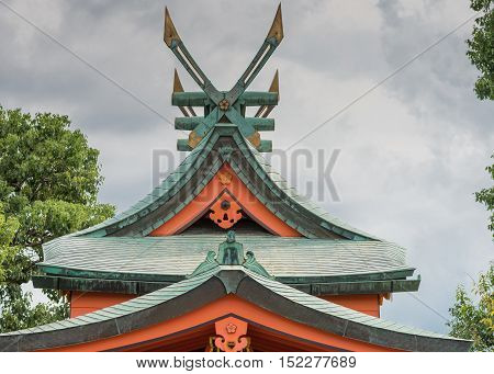 Kyoto Japan - September 17 2016: Windmill like roof structure at Fushimi Inari Taisha Shinto Shrine. Green tiles red facial boards cloudy sky fixed gold tipped wings.