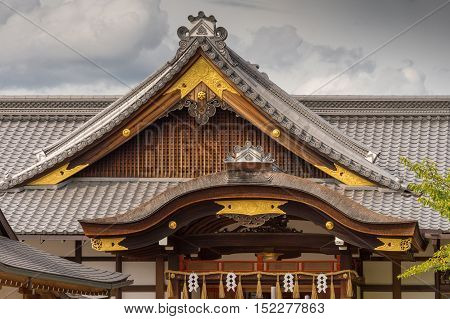 Kyoto Japan - September 17 2016: Two different shapes of roof structure at Fushimi Inari Taisha Shinto Shrine. Gray tiles brown facial boards and golden trim under cloudy skies.