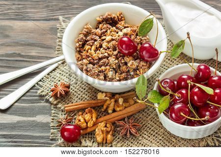 Homemade granola with cream cinnamon and cherries for breakfast on a wooden background