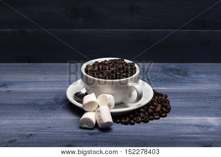Roasted coffee beans in a white ?up marshmallows sugar cubes and spoon on vintage wooden background. Side view