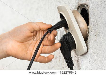 hand using broken dangerous old electric socket