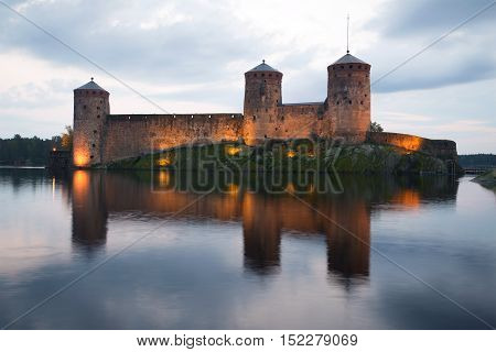 Towers of the medieval fortress Olavinlinna in the background of the cloudy sky. Twilight August in Savonlinna, Finland