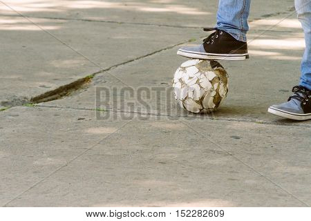 The foot of a young steps on a football on the asphalt