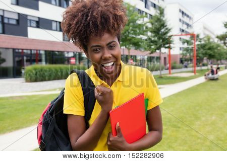 Happy african american female student outdoor on campus of university in the summer
