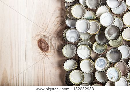a lot of beer caps on a wooden board top view