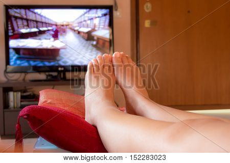 close-up on the feet of a girl watching TV