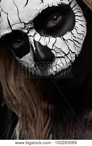 Beauty Woman with scary Skull on her Face. Devil Halloween Face Art Concept