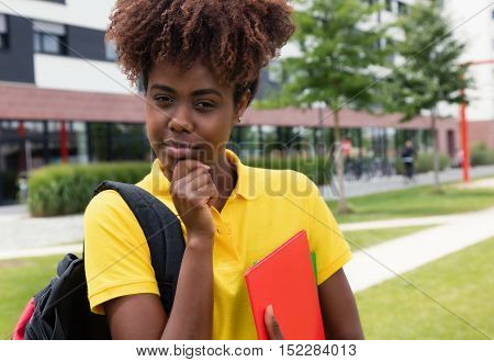 Smart african american female student outdoor on campus of university in the summer
