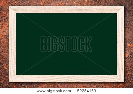 Chalkboard or Empty bulletin board with a wooden frame on rusty metal background with copy space for text or image.