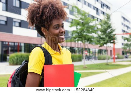 African american female student walking outdoor on campus of university in the summer