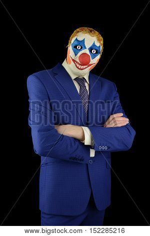 man in a business suit and in a terrible clown mask on a black background