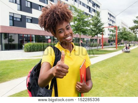 African american female student showing thumb outdoor on campus of university in the summer
