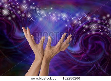 Sensing Supernatural Electromagnetism - Female energy worker with hands outstretched and open upwards towards stream of sparkles on a dark machine-like spiraling  formation background