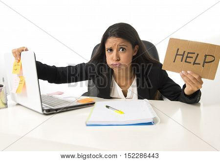young busy desperate Latin businesswoman holding help sign sitting at office desk in stress worried and overwhelmed working at office computer desk in deadline pressure and overtime