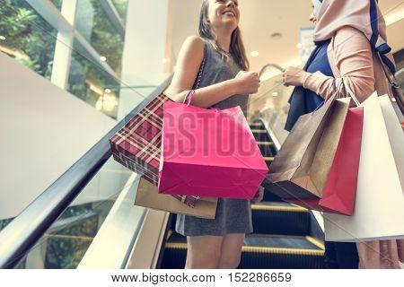 Women Going Up Escalator Concept