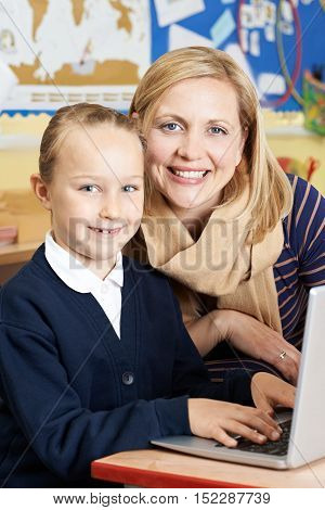 Teacher Helping Female Elementary School Pupil In Computer Class