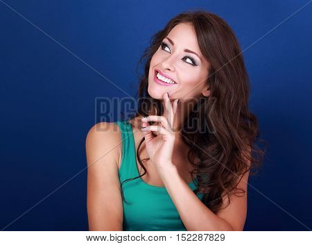 Thinking Success Beautiful Brunette Woman With Finger Under Face Looking Up On Blue Background
