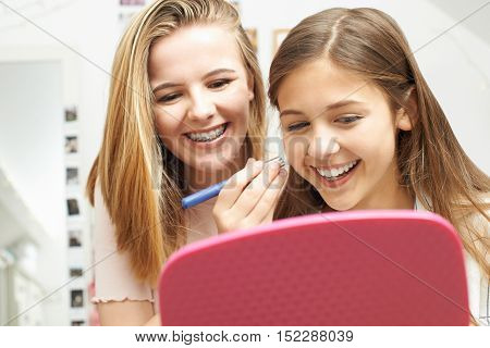 Two Teenage Girls Putting On Make Up In Bedroom