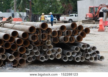 A stack of large steel pipes to be installed as a part of the water supply system of a building at construction site. Industry and construction concept.