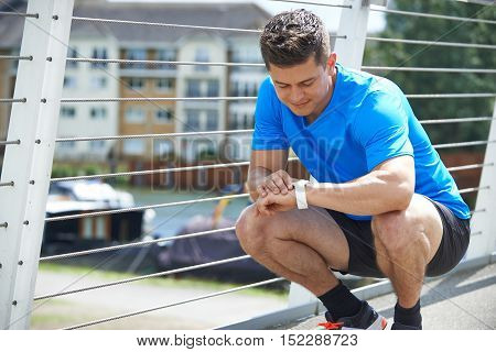 Man Looking At Activity Tracker Whilst Exercising In City