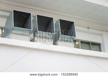 Multiple square industrial-grade air exhaust vents for an air cooling system at a facility. Industry and architecture concept.