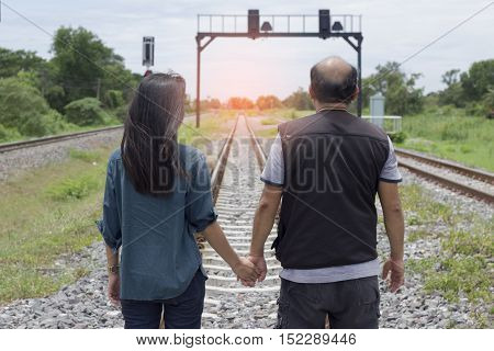 Romantic couple standing and hand-in-hand forever on railroad at sunrise or sunset