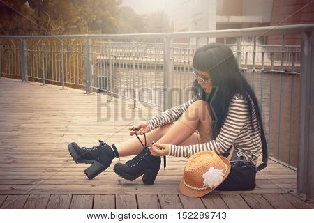 Woman sitting tying shoes  in public area