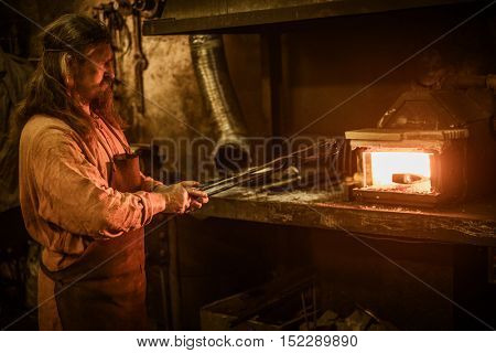 Senior blacksmith heats item before forgingin smithy