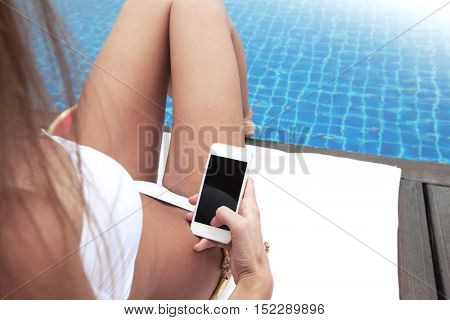 Woman sunbathing in chair by the pool and using mobile phone