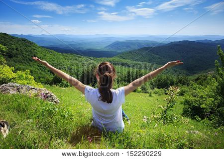 Happy young female traveller sitting at green grass glade at mountain landscape background in sunny spring day under blue cloudy sky with her hands up