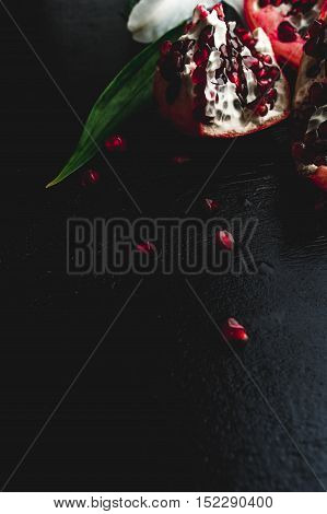 Delicious red pomegranate fruit on black background