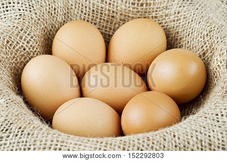 Fresh eggs placed in a bowl lined with burlap hessian cloth material